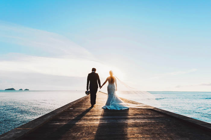 After their wedding, the bride and groom walk hand in hand along a jetty with the sea in the background