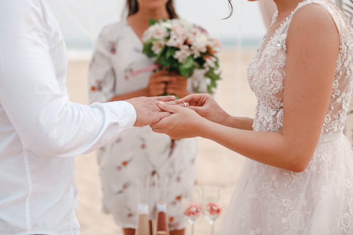 A couple hold hand and renew their wedding vows in a beach setting