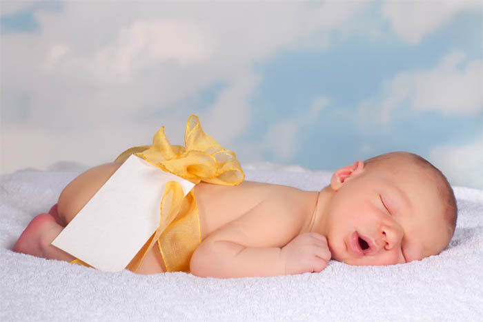 A cute baby, asleep, wearing a ribbon bow and naming day tag